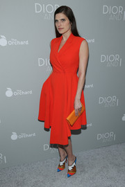 Totally embracing color, Lake Bell accessorized with an orange leather clutch.