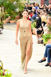 Bella Hadid glittered on the Oscar de la Renta runway in a strapless gold column dress.