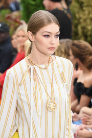 Gigi Hadid walked the Oscar de la Renta runway wearing an oversized cameo pendant.