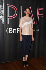 Marion Cotillard teamed her leather top with a pair of pinstripe capri pants.