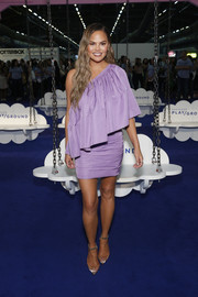 Chrissy Teigen was spotted at the Popsugar Play/Ground wearing a lavender one-shoulder dress by Solace London.
