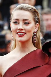 Amber Heard matched her red dress with a pair of dangling ruby and diamond earrings by Chopard.