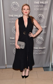 Natasha Lyonne styled her dress with a gray suede clutch.