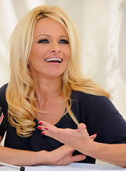 Pamela Anderson attended a press conference wearing her nails polished with a vibrant cherry red lacquer.