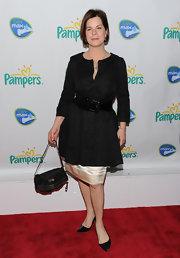 Marcia Gay Harden emphasized her waist in a loose top by wearing a thick patent leather belt at the Pampers Dry Max launch.