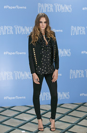 Cara Delevingne toughened up her star-print ruffle blouse with a black Saint Laurent military jacket for the 'Paper Towns' photocall.