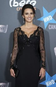 Penelope Cruz added glamour to her premiere look with Swarovski's black satin Party Time clutch.
