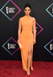 Emeraude Toubia kept it minimal yet stylish in a fitted orange one-shoulder gown by Solace London at the 2018 People's Choice Awards.