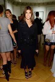 Carine Roitfeld teamed her button-down with a black fluted-hem skirt for a more feminine finish.