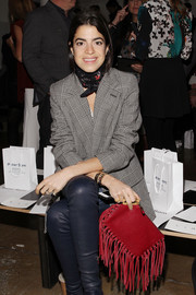 Leandra Medine attended the Peter Som fashion show carrying a fun-looking tasseled red clutch.