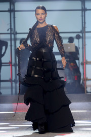 Adriana Lima worked an edgy-glam vibe with this black cold-shoulder gown with a lace bodice, a tiered skirt, and leather harness detailing at the Philipp Plein runway show.