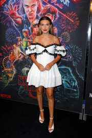 Millie Bobby Brown looked ultra girly in a white cold-shoulder dress with black ruffle detailing at the 'Stranger Things' season 3 photocall.