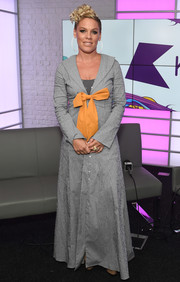 Pink stopped by KISS FM wearing a floor-length micro-print coat adorned with a large yellow bow.