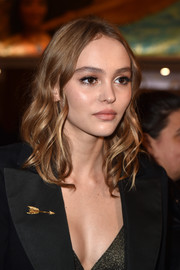 Lily-Rose Depp adorned her jacket with a gold arrow pin.
