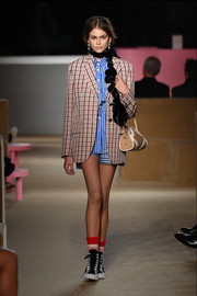 Kaia Gerber clashed prints with this plaid blazer and striped shirt combo at the Prada Resort 2020 runway show.
