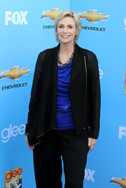 Jane wears a uniquely draped leather jacket over a blue blouse.