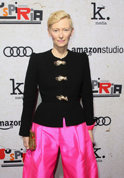 Tilda Swinton accessorized with a Schiaparelli Couture hand clutch (which matched the embellishments on her jacket) at the premiere of 'Suspiria.'
