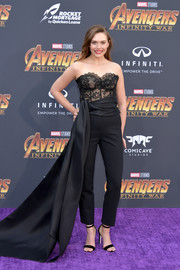 Elizabeth Olsen paired her top with high-waisted trousers, complete with a long side train.