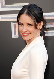 Evangeline Lilly wore a dressed-up ponytail to the 'Real Steel' premiere. To recreate her look, begin by setting dry hair on hot rollers. Next, make a two-inch section following the entire front hairline. Then finger comb hair back and secure into a ponytail. To finish the look, create a center part and push the remaining strands behind the ears.