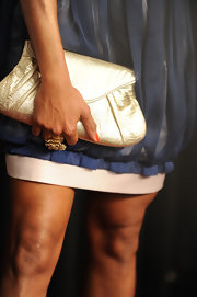 Regina King carried a lightweight gold clutch while attending a movie premiere. The metallic gold color really jumped off her navy blue frock.