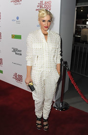 Gwen Stefani accented her fashion forward jumpsuit with a black hard case clutch with an oversize gold clasp.