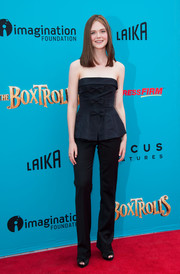Elle Fanning traded in her trademark girly pastels for a dark blue Oscar de la Renta peplum top, sweetened up with a row of bows down the front, when she attended the 'Boxtrolls' premiere.