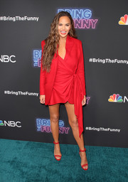 Chrissy Teigen popped on the teal carpet in a red wraparound blazer dress at the premiere of 'Bring the Funny.'