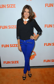 Daniella Monet attended the premiere of 'Fun Size' wearing a V-neck blouse with sheer sleeves.