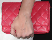 Paz Vega added some color to her all-white look with a red quilted clutch.