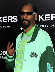 Snoop Dogg paired his green varsity jacket with square sunglasses.