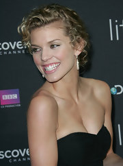 AnnaLynne's highlighted blond ringlets are pinned in a fun and feminine updo with small pieces left out to frame her face. This look is completed with a dazzling pair of diamond drop earrings.