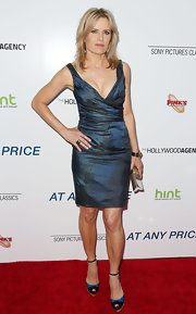 Kim Dickens chose a metallic frock with a gathered waist and plunging neck for her sleek and sexy red carpet look at the premiere of 'At Any Price.'