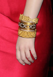 Emma Stone accented her red satin dress with bold gold bangle bracelets.