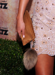 This tan leather wrislet certainly has an unexpected factor about it. Don't think the rabbit tail is very common on handbags, but the fur trend does seem to be picking up pretty fast.