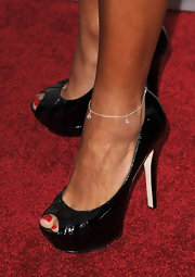 Karina showed off her golden legs in a pair of peep-toe pumps, which perfectly matched her patent leather black clutch.