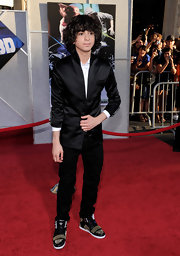 Adam hit the red carpet sporting a satin blazer with skinny jeans and studded high top sneakers.