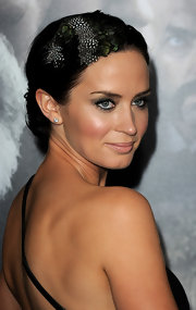 Emily Blunt stunned with a pinned updo accessorized with a feathered hair piece.