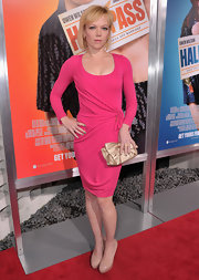 Emily Bergl added glamour to her look with a metallic gold clutch adorned with an oversize bow.