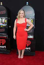 Amy Poehler went bold in a form-fitting, cleavage-flaunting scarlet dress by Victoria Beckham at the premiere of 'The House.'