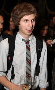 The hilarious Michael Cera sports a backpack with his skinny, stiped, grey and red tie. Nice.