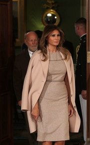 Melania Trump styled her dress with a pale pink wool coat by Acne Studios.