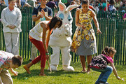 (AFP OUT) U.S. first lady Michelle Obama (R) gives encouragement to her daughter Malia Obama (3rd R) and other children during the White House Easter Egg Roll on the South Lawn of the White House April 25, 2011 in Washington, DC. About 30,000 people are expected to attend the 133-year-old tradition of rolling colored eggs down the White House lawn.