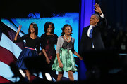 Sasha Obama looked very girly in her gray cardigan, bow-embellished blouse, and print skirt during her father's victory celebration.