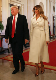 Melania Trump styled her coat with a pair of copper-hued pumps.