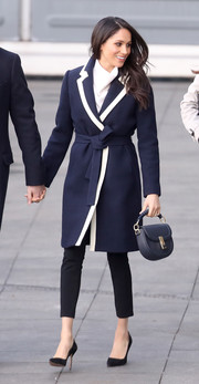 Meghan Markle topped off her look with a navy leather purse by Altuzarra.