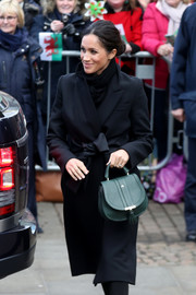 Meghan Markle paired a forest-green Demellier London purse with a black coat for her visit to Cardiff Castle.