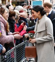 Meghan Markle accessorized with a simple yet stylish brown leather purse by Charlotte Elizabeth during her visit to Belfast.