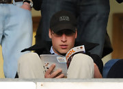 Prince William tossed on a black baseball cap while watching a match in England.