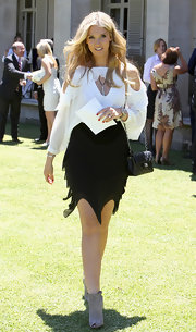 Delta Goodrem finished off her bold ensemble with a pair of nude peep-toe ankle boots.