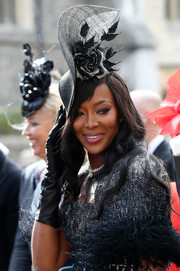 Naomi Campbell accessorized with a dramatic black floral fascinator at Princess Eugenie's wedding.